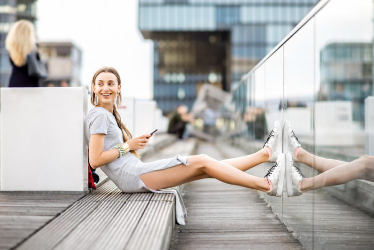 Lifestyle portrait of a business woman dressed casually sitting with phone outdoors at the modern district in Dusseldorf city, Germany